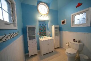 Blue bath with fun beachy decor and nautical windows.