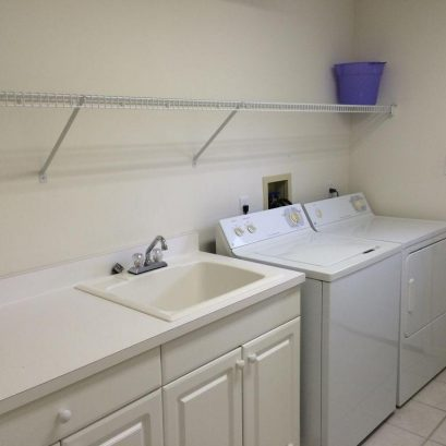 Downstairs Laundry Room with sink, shelves, and room to fold clothes
