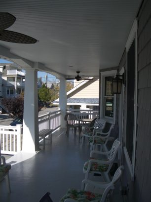 """Large front porch with many outdoor chairs, tables, seats for """"porch living"""""""