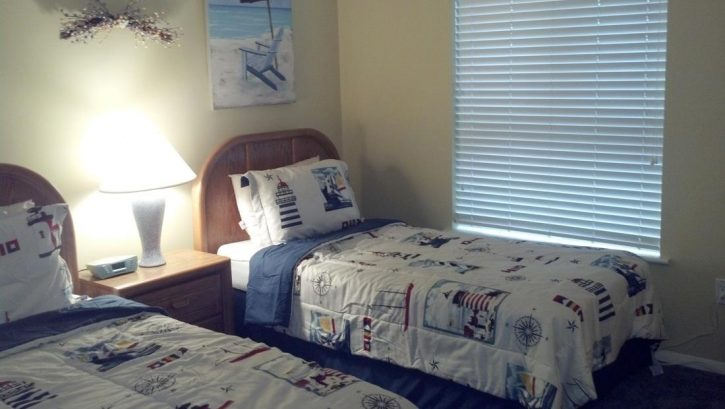 upstairs twin bedroom with tv, ceiling fan, ocean views