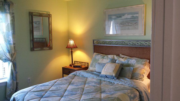 upstairs queen bedroom with tv, ceiling fan, ocean views