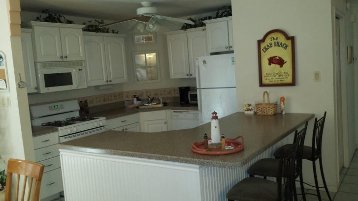 Large, fully equipped kitchen with bar seating, ceiling fan
