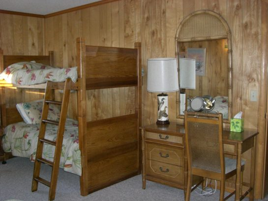 Upper level master bedroom has three twin beds, set of bunk beds, and desk