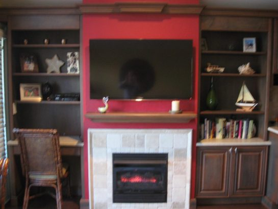 Living area with large TV, gas fireplace, and desk area