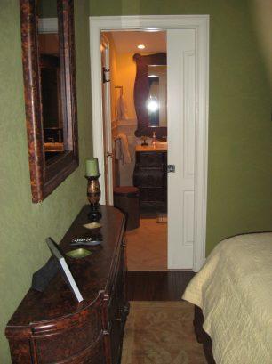 Pocket door through to bathroom, bedroom TV behind mirror, additional storage