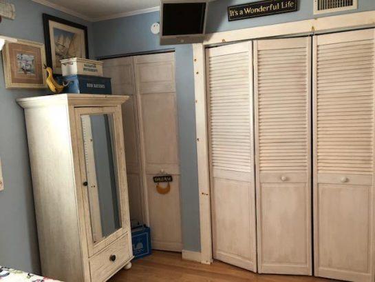 Adjustable flat screen TV in bedroom with lots of closet storage