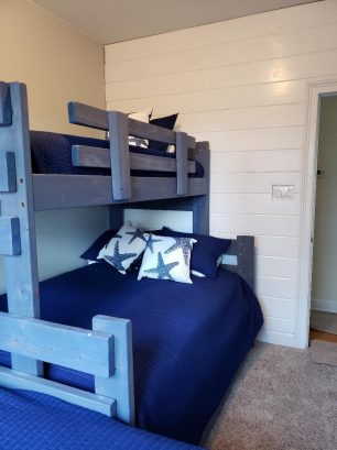 View of Bunk room with full bed on bottom and twin on top, plus a  pull-out twin trundle under the bunk.  The room also has another stand alone twin bed by the window.