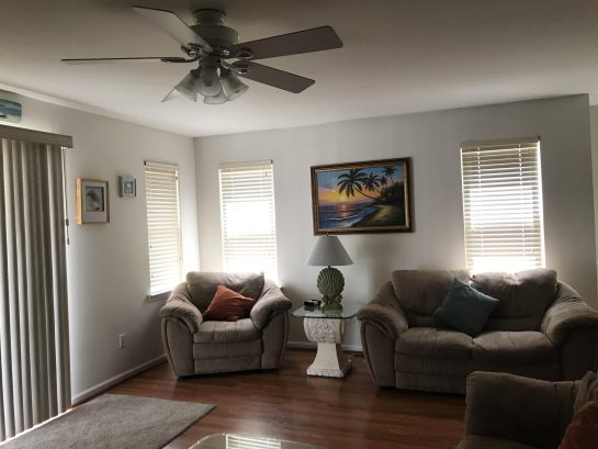 Living room area with plenty of seating, large screen TV and ceiling fan