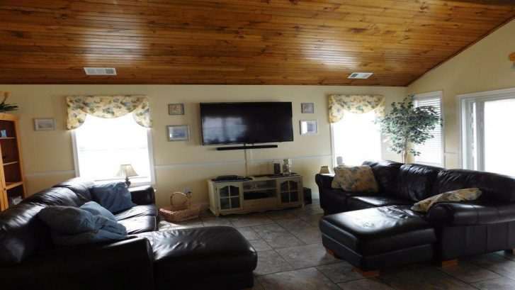 "Spacious living room, wooden cathedral ceiling, 55"" TV and new sliders to deck"