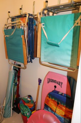 Storage closet with chairs, umbrellas and toys for your use.