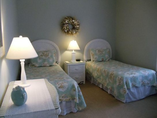 Third bedroom has 2 twin beds, night table, dresser, closet, and wicker chair