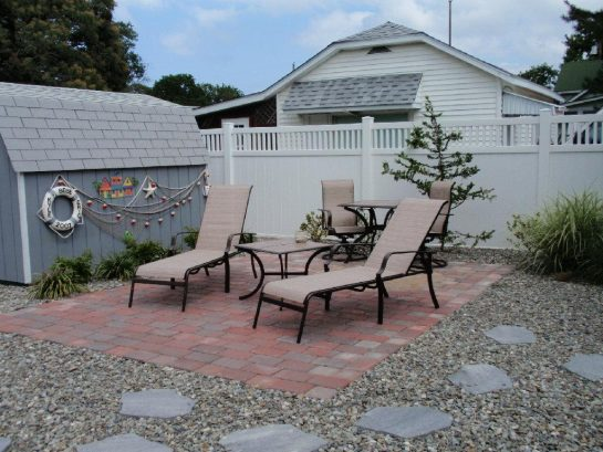 Backyard Paver patio with Lounge chairs and Umbrella has been added
