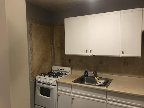 Kitchen with stove, sink, cabinets, and fridge