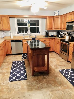 Granite center island adds even more space for food prep while enjoying perfect stainless steel appliances.