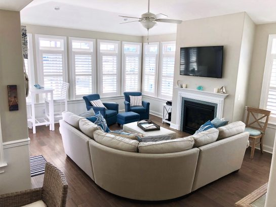 "Family room from kitchen, 55"" cable TV, plenty of comfy seating, streaming light from lots of windows, plantation shutters"