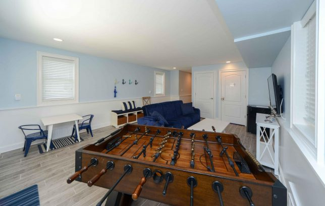 Ground level entryway recreation room with futon sofa, TV, foosball table, stairwell, elevator, garage