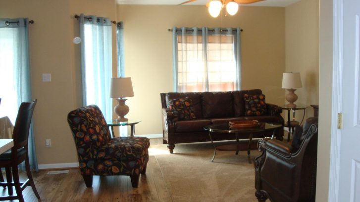 Comfortable living area with leather furniture and new hardwood flooring.