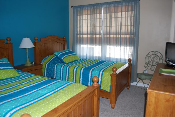 Bedroom #2 with TV/DVD Player.  Window looks out onto patio/pool area.