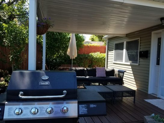 covered porch with seating and gas grill