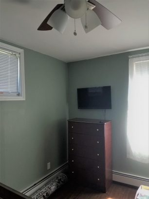 bedroom #2 with TV, ceiling fan and window a/c
