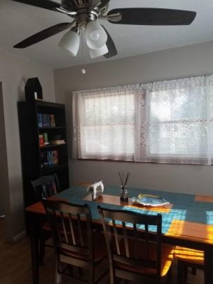 dining room with ceiling fan & window a/c